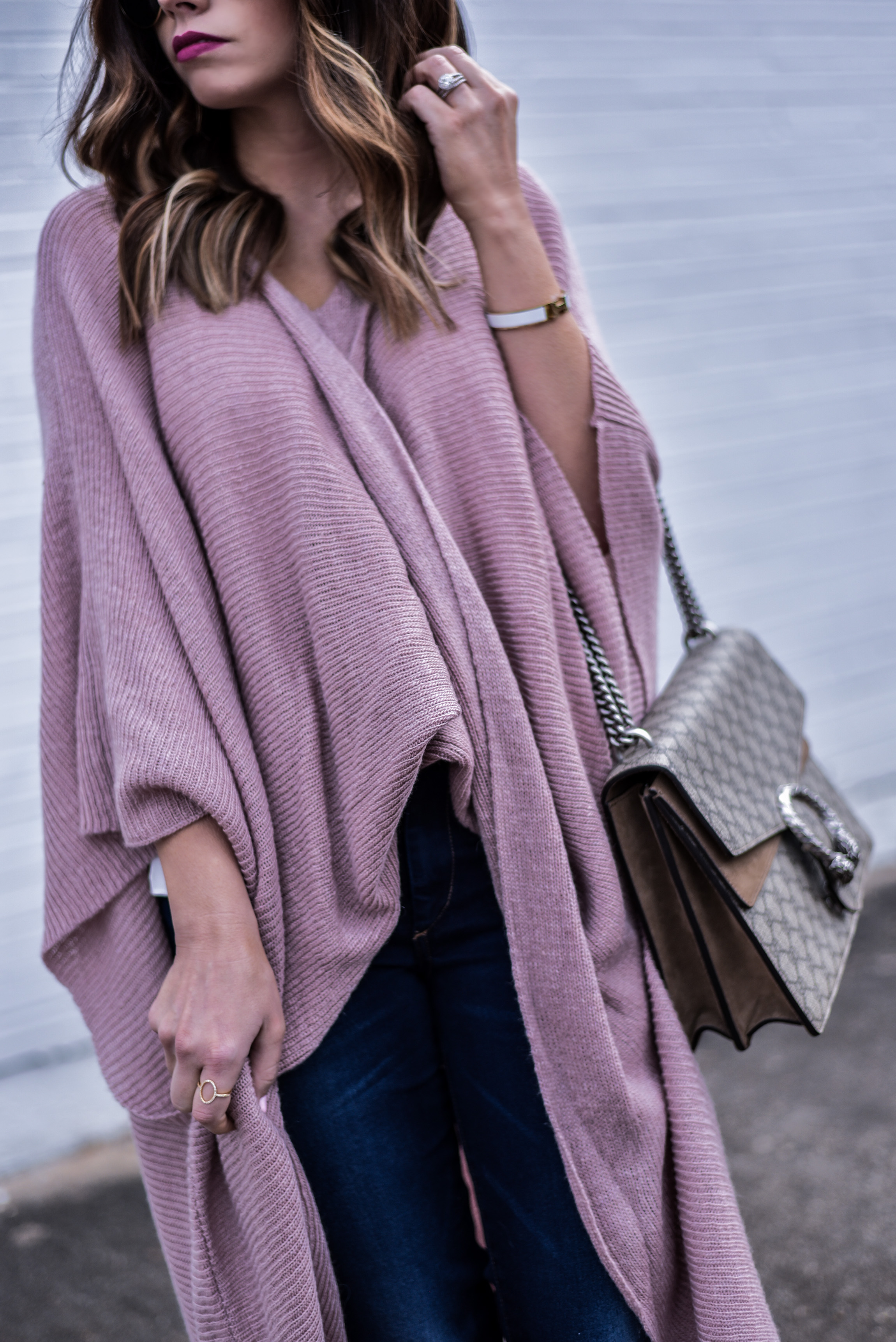 Tiffany Jais the Houston style blogger of Flaunt and Center wearing a wrap poncho from anthropology and dark wash skinny jeans with steve madden heels, and a gucci bag | what's trending in fashion