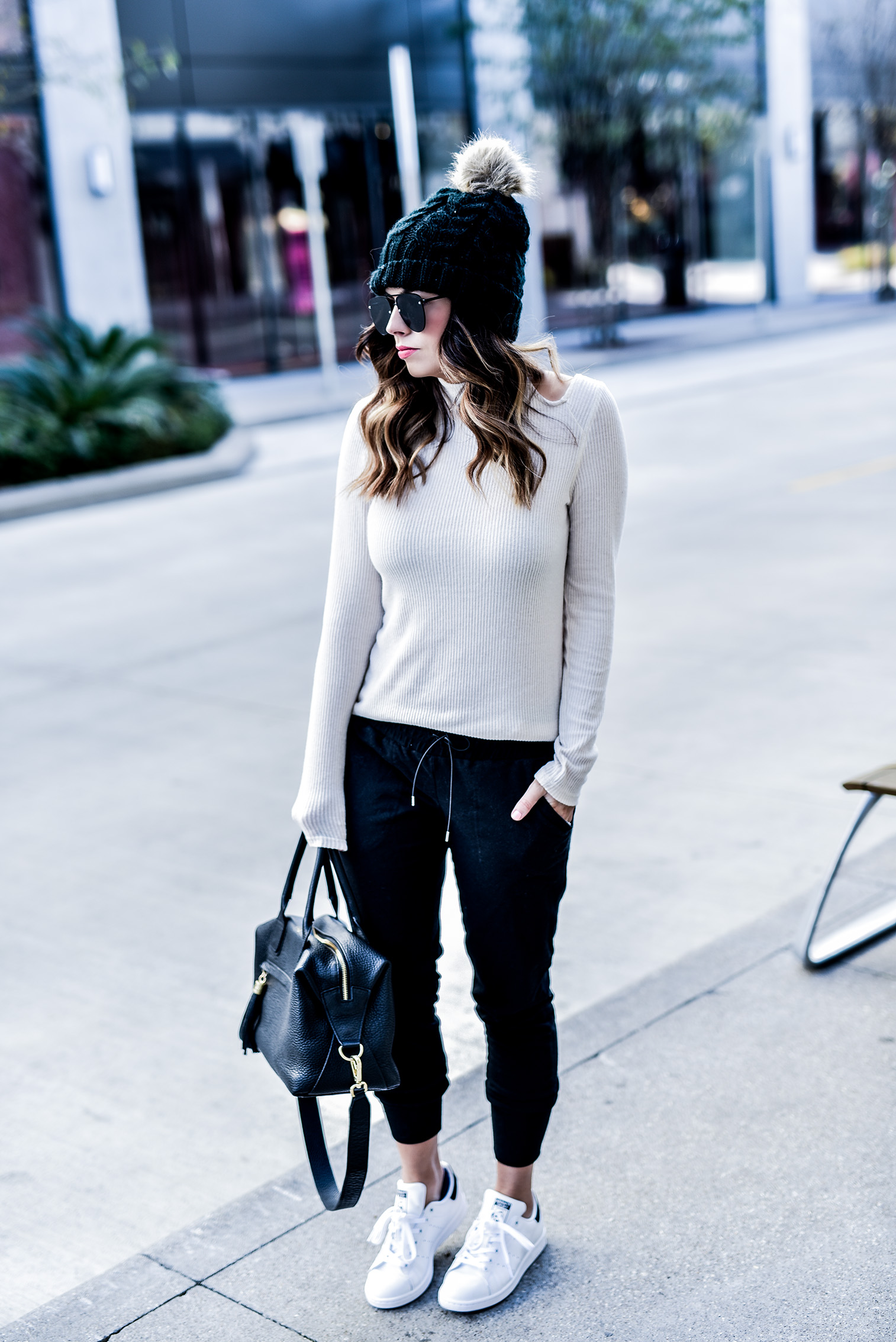 Fashion and lifestyle blogger Tiffany Jais sharing 5 reasons to love joggers | She is wearing free people skinny black joggers, Stan Smith sneakers, a white cutout sweater by Revolve, and a faux fur pom pom beanie | streetstyle fashion, women's fashion