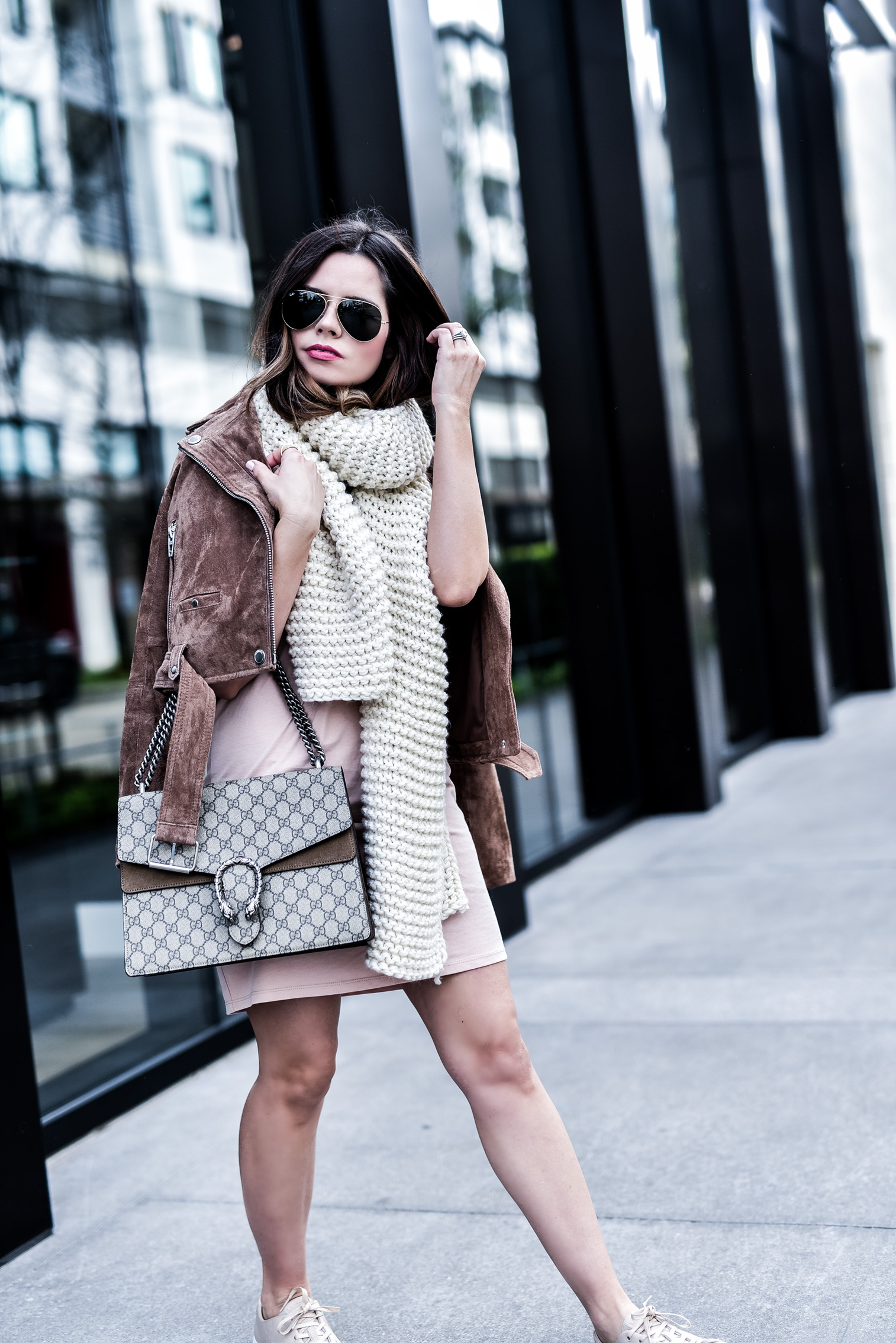 Houston fashion blogger wearing an asos pink dress and a blank nyc suede moto jacket, read up on how to concur effortless casual style by clicking this photo   Gucci Dionysus bag, chunky knit scarf, sneakers and a dress