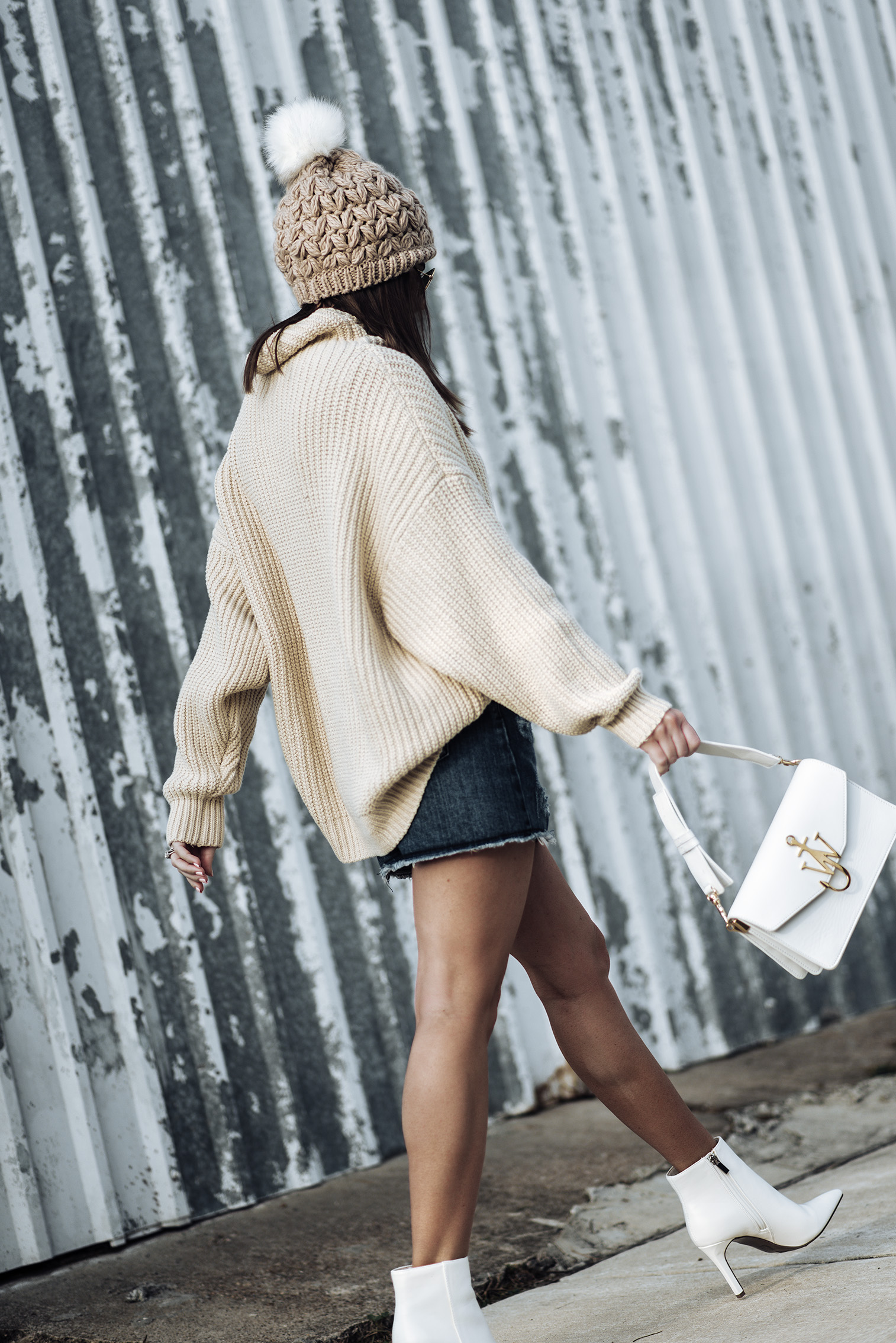 All white accessories  Free People swim too deep sweater   Evidnt denim skirt   White ankle boots (similar)   Pom pom beanie (this years version)   J.W. Anderson logo bag in white  Tiffany Jais fashion and lifestyle blogger of Flaunt and Center   Houston fashion blogger   Straw handbag Trend   Streetstyle blog #streetstyle #sweateroutfits #denimskirtoutfits #falloutfits2017 #falloutfits